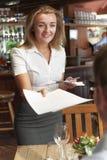 Menu del cliente di In Restaurant Handing della cameriera di bar fotografia stock libera da diritti