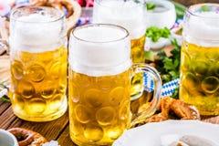 Menu dell'alimento di Oktoberfest, salsiccie bavaresi con le ciambelline salate, purè di patate, crauti, birra fotografie stock libere da diritti