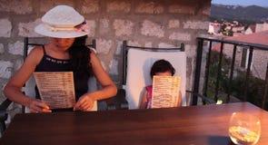 Menu della lettura della bambina e dell'adulto Fotografia Stock