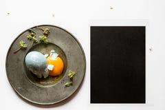 Menu do ajuste de lugar da Páscoa com ovo quebrado, azul tingido Imagens de Stock