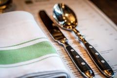 Menu do guardanapo de linho da cutelaria da faca e da colher na tabela Foto de Stock