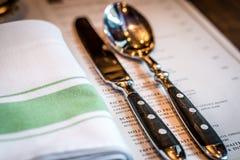 Menu do guardanapo de linho da cutelaria da faca e da colher na tabela Imagem de Stock Royalty Free