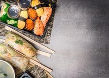 Menu do sushi com rolos do verão, nigiri e molho de soja no fundo de pedra cinzento, vista superior Foto de Stock