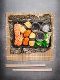 Menu do sushi com rolos e nigiri na caixa plástica do transporte com hashis Fotos de Stock