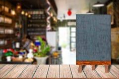 Menu en bois de signe de tableau noir de cadre de tableau sur la table en bois, fond brouillé d'image Image stock