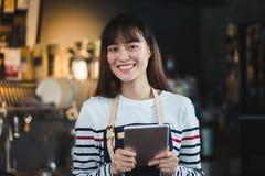 Menu fêmea asiático do café do tablet pc da posse do avental do desgaste do barista com a cara de sorriso na ordem de espera do c fotografia de stock