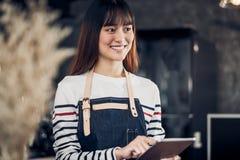 Menu femelle asiatique de café de tablette de prise de tablier d'usage de barman avec le visage de sourire dans l'ordre de attent images libres de droits
