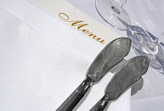 Menu and fish knives. Angled shot of a menu with two fish knives and the bases of two stemware glasses Stock Images