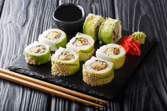 Menu green dragon Japanese rolls with avocado, omelet, sesame and cucumber closeup. horizontal royalty free stock image