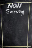 Menu of now serving. Written with chalk on a blackboard Stock Image