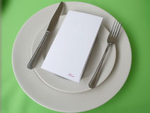 Menu over plate with copy space. The menu over plate with copy space over a green table cloth Royalty Free Stock Photography