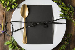 Menu place setting with empty card and golden spoon over wooden background, surrounded by green branches Royalty Free Stock Image
