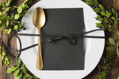 Menu place setting with empty card and golden spoon over wooden background, surrounded by green branches Royalty Free Stock Images