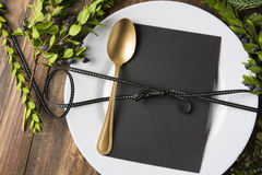 Menu place setting with empty card and golden spoon over wooden background, surrounded by green branches Stock Photography