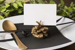 Menu place setting with empty card and golden spoon over wooden background, surrounded by green branches Stock Photos