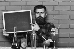 Menu for pub or bar. Barman with beard and serious face holds blank blackboard, chalkboard,. Copy space. Man near cocktails on brick wall background Royalty Free Stock Photo