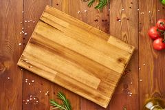 Menu, recipe, mock up, banner. Food seasoning background. Spices, Herbs and wooden cutting board on brown dark wooden backdrop. Top view, copy space stock photos