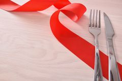 Menu for restaurant with cutlery ribbon on wood table elevated. Menu background for restaurant with silver cutlery and red ribbon on wood table background Stock Images