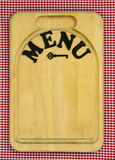 MENU sign on wood cutting board with red checkered tablecloth. MENU sign with iron key on wooden cutting board with red gingham background Stock Photos