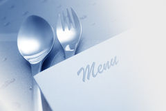 Menu with spoon and fork. On a glass table Royalty Free Stock Photo