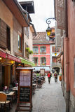 Menu and tables on narrow street among typical colorful houses. ANNECY, FRANCE - JUNE 26, 2014: Menu and tables on narrow street among typical colorful houses Stock Image