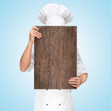 Menu template. Restaurant chef hiding behind a wooden chopping board for a business lunch menu with prices Royalty Free Stock Photo