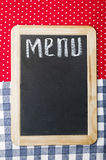 Menu. Title written with chalk on blackboard lying on tablecloth red polka dot Royalty Free Stock Photo