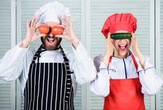 Menu vegetariano Uomo e donna che giocano con le verdure naturali nella cucina del ristorante Tenuta senior dell'assistente e del fotografia stock