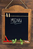 Menu written with chalk on aged blackboard with chili peppers and parsley hanging on wooden wall Stock Photos