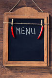Menu written with chalk on aged blackboard with chilli peppers hanging on wooden wall Stock Images