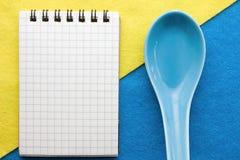 Menuachtergrond Kok Book Receptenblocnote met okkernoten op een blauwe en gele achtergrond Stock Fotografie