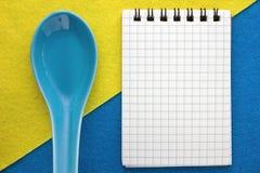 Menuachtergrond Kok Book Receptenblocnote met okkernoten op een blauwe en gele achtergrond Stock Foto's