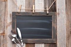 Menubord met vork, lepel en mes op houten achtergrond stock foto's