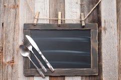 Menubord met vork, lepel en mes op houten achtergrond royalty-vrije stock afbeelding
