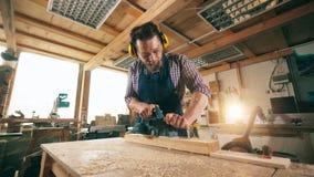 Menuiserie avec du bois sciant d'artisan Artisan travaillant en menuiserie banque de vidéos