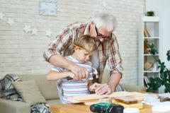 Menuiserie de enseignement de garçon de vieil homme Photographie stock libre de droits
