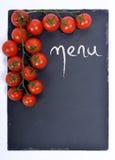 Meny på en svart tavla med tomater Arkivfoton