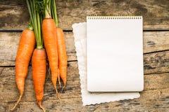 Menybakgrund Grönsaker på tabellen med kockboken Matlagning med receptboken Royaltyfri Bild