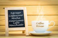 Menykaffe på den svarta svart tavlan med varmt kaffe i den vita koppen och Arkivfoto