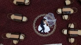Menzogne abbracciando le coppie della persona appena sposata sul tappeto rosso nell'albergo di lusso Lo sposo sta baciando tenero stock footage