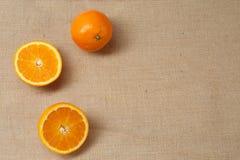 Menzogne arancio fresca su una superficie della tela di sacco Immagini Stock