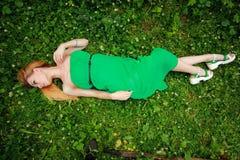 Menzogne bionda fine sull'erba, meravigliosamente piegato, guardante giù, Immagini Stock Libere da Diritti