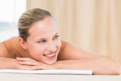 Menzogne bionda pacifica sull'asciugamano che sorride alla macchina fotografica Fotografia Stock