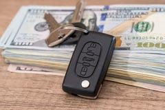 Menzogne chiave dell'automobile sulle banconote in dollari degli Stati Uniti 100 Immagini Stock Libere da Diritti
