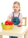 Menzogne della bambina smontata in un canestro di frutta Immagine Stock