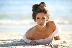 Menzogne di modello incline sulla spiaggia Fotografia Stock Libera da Diritti