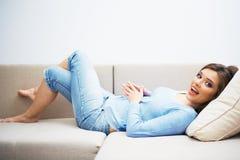 Menzogne di rilassamento del sofà della giovane donna Fotografia Stock