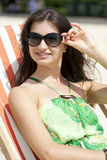 Menzogne di rilassamento della bella donna su una chaise-lounge del sole Fotografie Stock