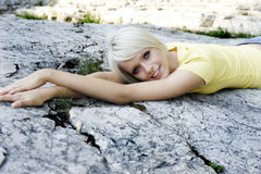 Menzogne di rilassamento della bella donna su una roccia Fotografie Stock