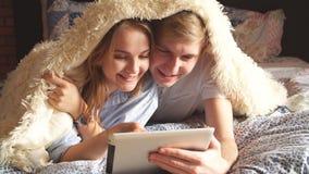 Menzogne di risata delle coppie amorose sul letto e per mezzo della compressa stock footage